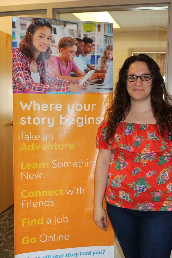 Marketing intern Katie Martel standing next to a banner. Spring 2019 Internship.