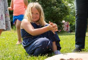 Young girl sitting in grass smiling at a library event during summer learning